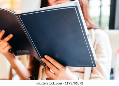 Woman seeing inside blue cover menu and considering for making order.