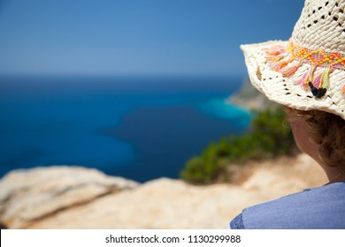 Woman seen from behind looking at a sea landscape from a cliff
