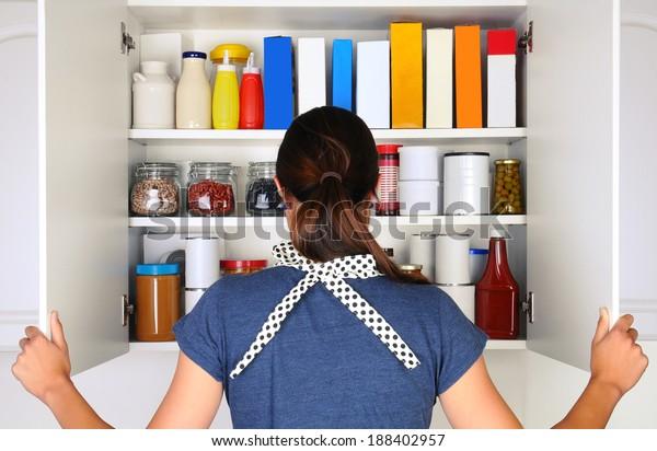 Una mujer vista desde atrás abriendo las puertas a una despensa llena. El armario está lleno de varios alimentos y comestibles, todos con etiquetas en blanco. El formato horizontal de la mujer es irreconocible.