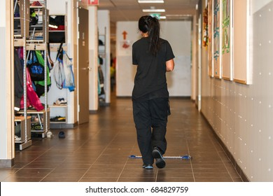 A woman, seen from behind, is sweeping and cleaning the floors in a school corridor.