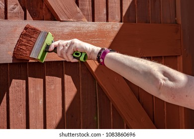 Woman seen painting a timber built gated entrance with a large, timber paintbrush. This shallow focus image is of the paint brush itself as it paints in a horizontal manner,