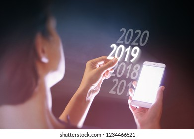 Woman select 2019 on her smartphone. New 2019 year in high tech.