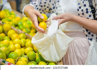 woman is selecting fruits in cotton bag at local food market. zero waste shopping concept
