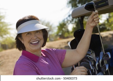 Woman selecting golf club from golf cart, smiling, (portrait)