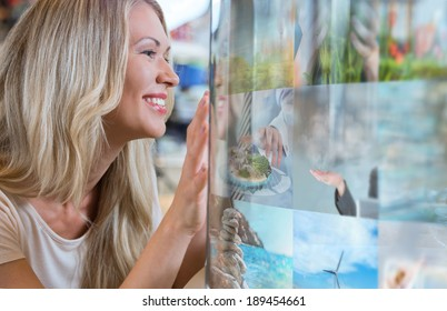 Woman selecting tv channel on glass touch screen