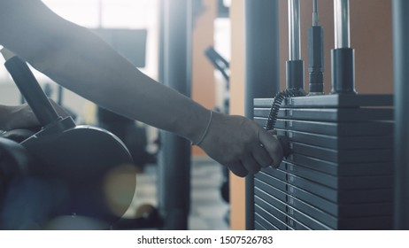 Woman selecting weight on a lat pulldown machine, sports equipment concept