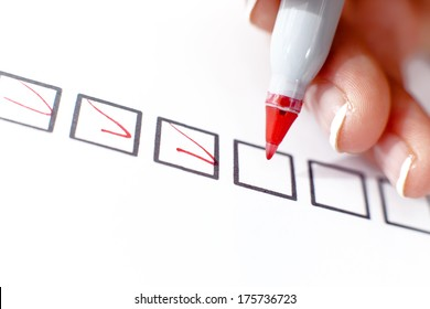 A woman selects and marks in the top box of a series.