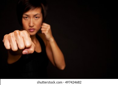 Woman self defense punching at the camera.  Selective focus.  Asian woman doing martial arts workout. Woman exercising, expressing aggression. Fitness model isolated on a black background.
