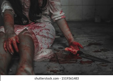 Woman self harming with knife. Woman hand holding a bloody knife. Hand full of blood and wrist cut. Halloween concept. Horror and Scary concept.