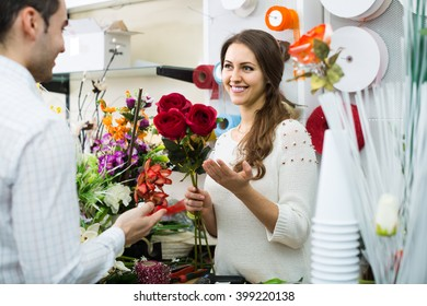 Woman seller helping to pick floral bouquet of flowers client at flower shop