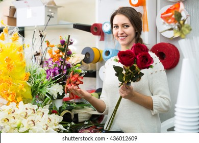 Woman seller helping to pick floral bouquet of flowers