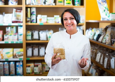 Smiling  woman seller in uniform holding cereals products in hands in pharmaceutical store