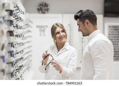 Woman selling eyeglasses to customer man in glasses store