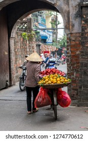 Woman is selling fruits from bicycle on the street in Hanoi, Vietnam - December 23, 2018 Street vendor in Hanoi, Vietnam is selling fruits from his bicycle.