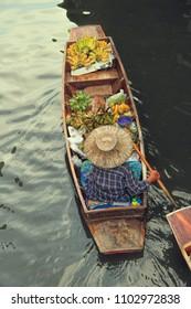Woman selling fruits at Damnoen Saduak Floating Market, Bangkok, Ratchaburi,ni Thailand