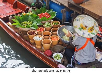 A woman selling Papaya salad Bangkok floating market.