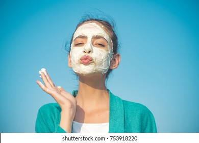 Woman send air kiss with cosmetic mask on face on blue sky. Beauty, nature, youth, skin care, rejuvenation concept - Shutterstock ID 753918220
