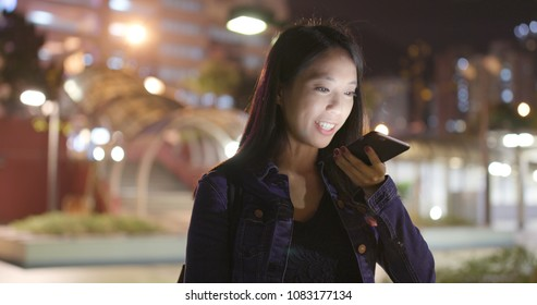 Woman sending audio message on smart phone at outdoor