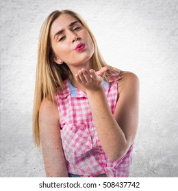 Woman sending a kiss on textured background