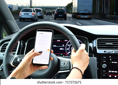 Woman sending message from a smartphone while driving a car