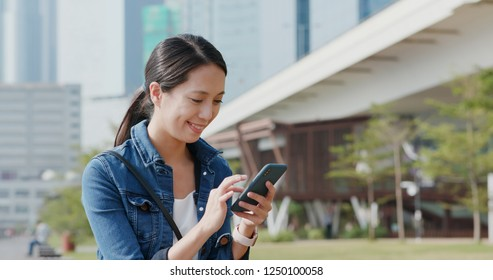 Woman sending text message on mobile phone at park