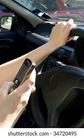 Woman sending a text message while driving a car