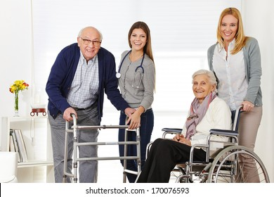 Woman with senior couple at home getting help from a caregiver