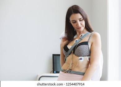 Woman with sensors of holter monitor device for daily monitoring of an electrocardiogram on her body. Treatment of heart diseases. Health control.