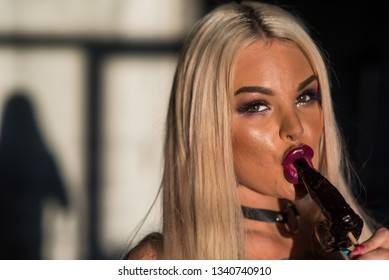 Woman with sensual lips holding dick lollipop. Blonde sucks a lollipop for adults