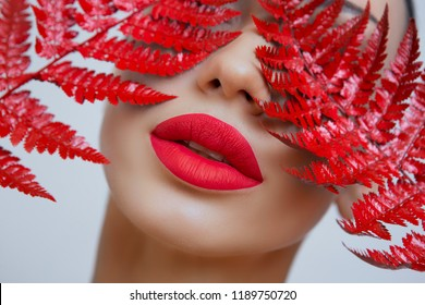 A woman with Sensual red lips and a fern. Woman's mouth with Sexy red Lips. Sexy woman matt Red Lips on a Gray background. Female portrait with bright makeup. matt lipstick