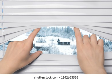 Woman separating slats of blinds and looking through window at beautiful landscape