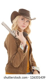 A woman with a serious expression on her face holding her gun on her shoulder.
