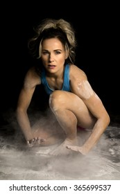 A woman with a serious face in her fitness clothing, getting covered in chalk.