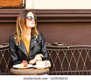 Woman with serious face spends time in cafe. Girl in sunglasses near tasty berry cake and coffee on brown terrace background. Lady drinks coffee during coffee break. Desserts and lunch time concept