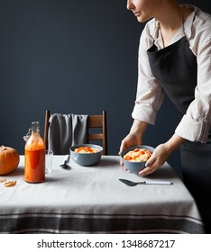 Woman serve breakfast table with vegan pumpkin porridge and fresh juice in Scandinavian style on grey background.