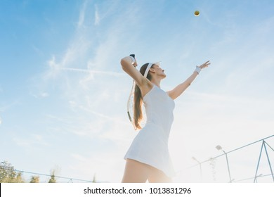 Woman serving the ball for a game of tennis on court