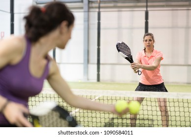 Woman serving balls to other in paddle tennis class