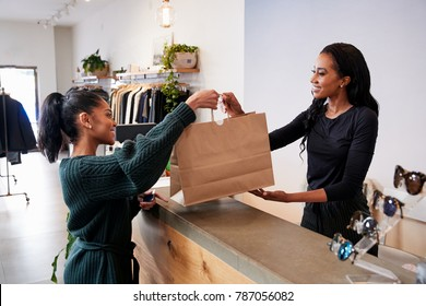 Woman serving customer at the counter in a clothing store