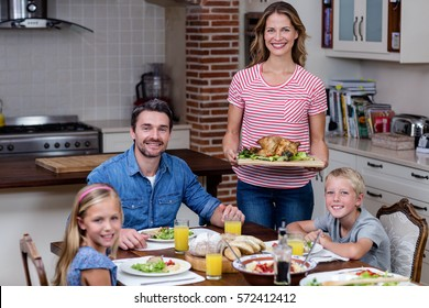 Woman serving food to her family in the kitchen at home