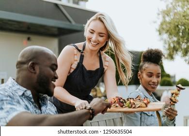 Woman serving her friends vegan barbeque skewers