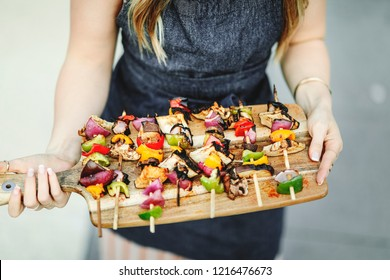 Woman serving vegan barbecue skewers on a wooden board