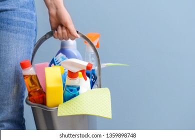 Woman with set of cleaning supplies on color background