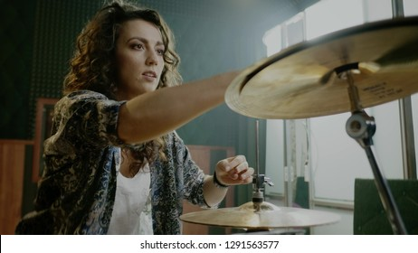 Woman setting drums during music band rehearsal