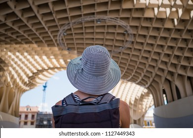Woman in Seville, Spain, with Metropol Parasol in the background. Life style people.