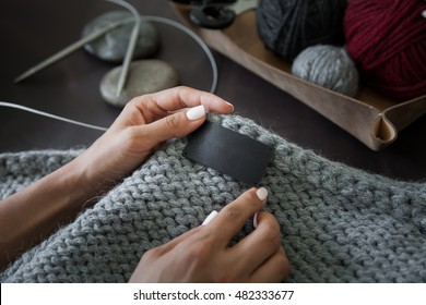 Woman sewing the blank genuine leather label on knitted clothing. Empty tag for your logo. Unrecognizable, closeup, hands only, mockup.