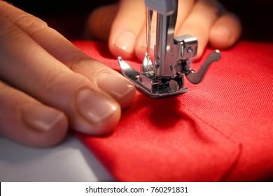 Woman sewing on machine, closeup