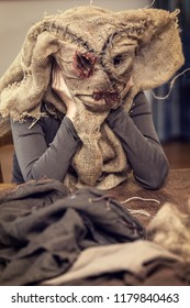 woman is sewing a scarecrow mask and costume for carneval or halloween, maybe a prop for a movie or theatre