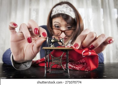 Woman sewing with a small sewing machine, humorous photography