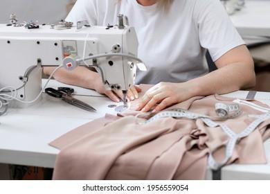 Woman sews behind sewing machine at work