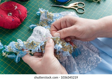 A woman sews a decorative element to clothes with a needle